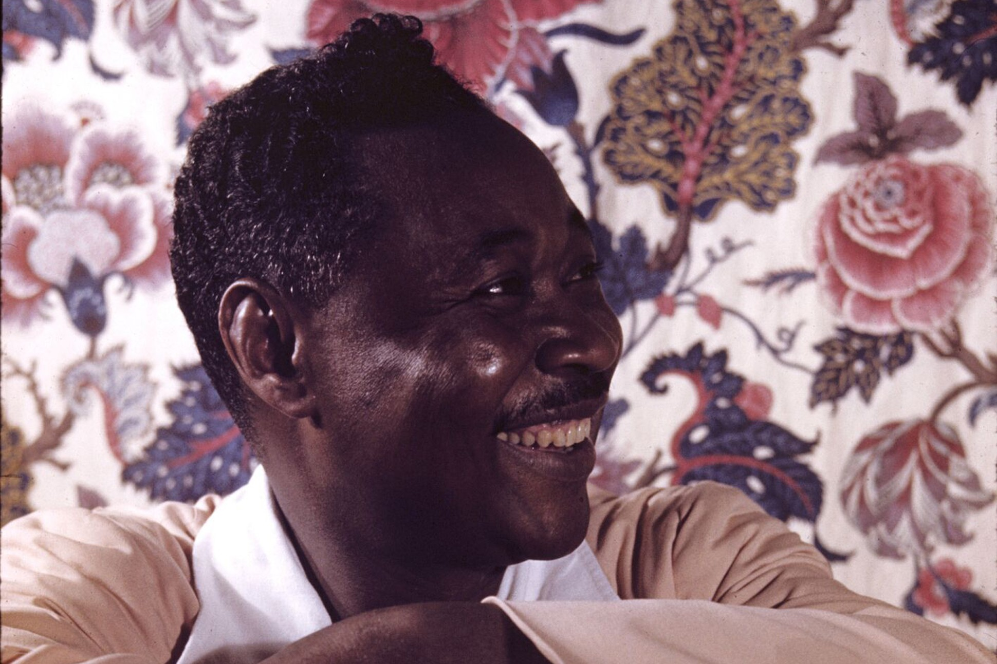 Photograph of Claude McKay in front of a floral background.