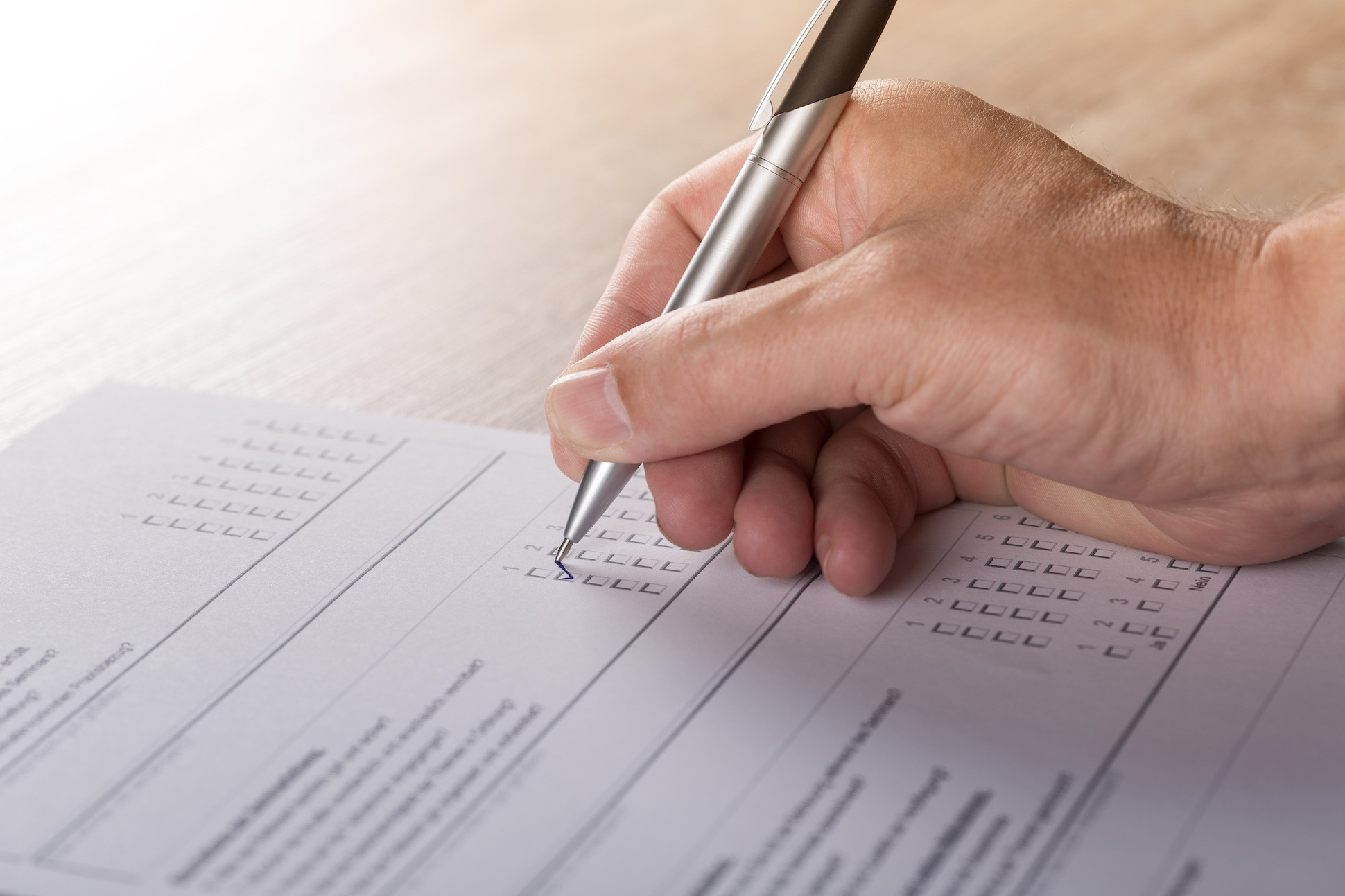 Image of hand checking off boxes on a standardized test sheet.