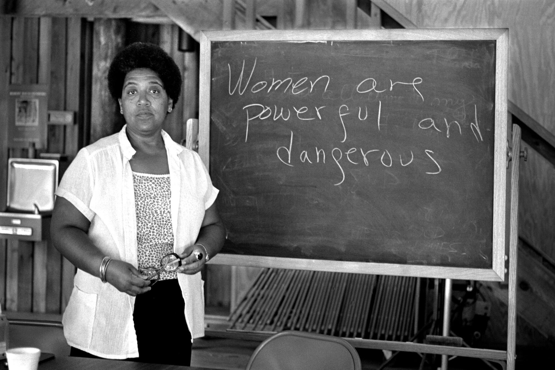 Audre Lorde standing next to a chalkboard where she has written Women are powerful and dangerous