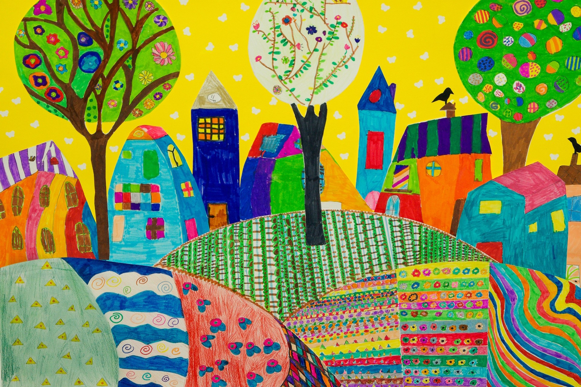 Image of colorful children's drawing, featuring several houses and a park.