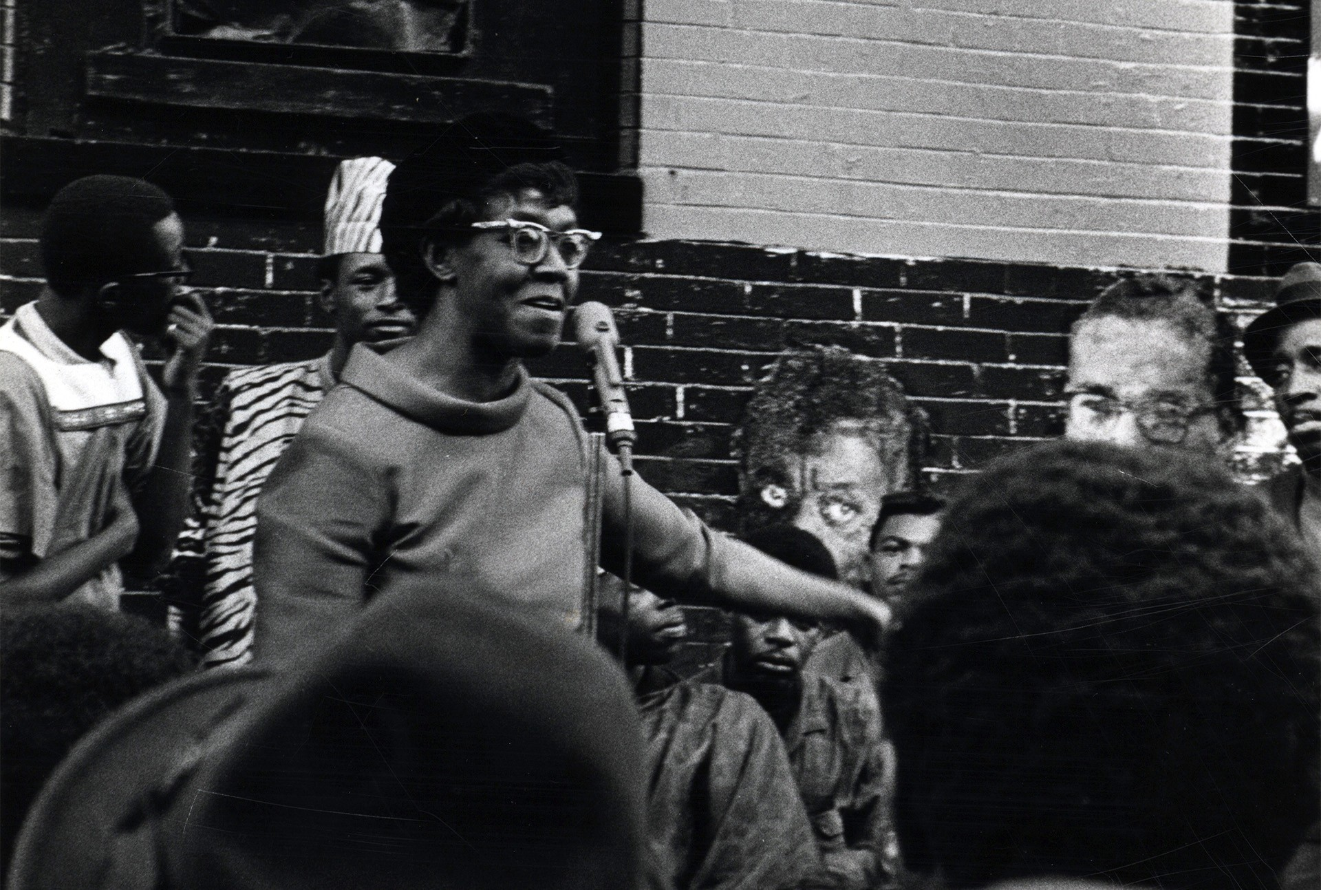 Black and white photograph of the poet Gwendolyn Brooks speaking at the Wall of Respect in 1967.