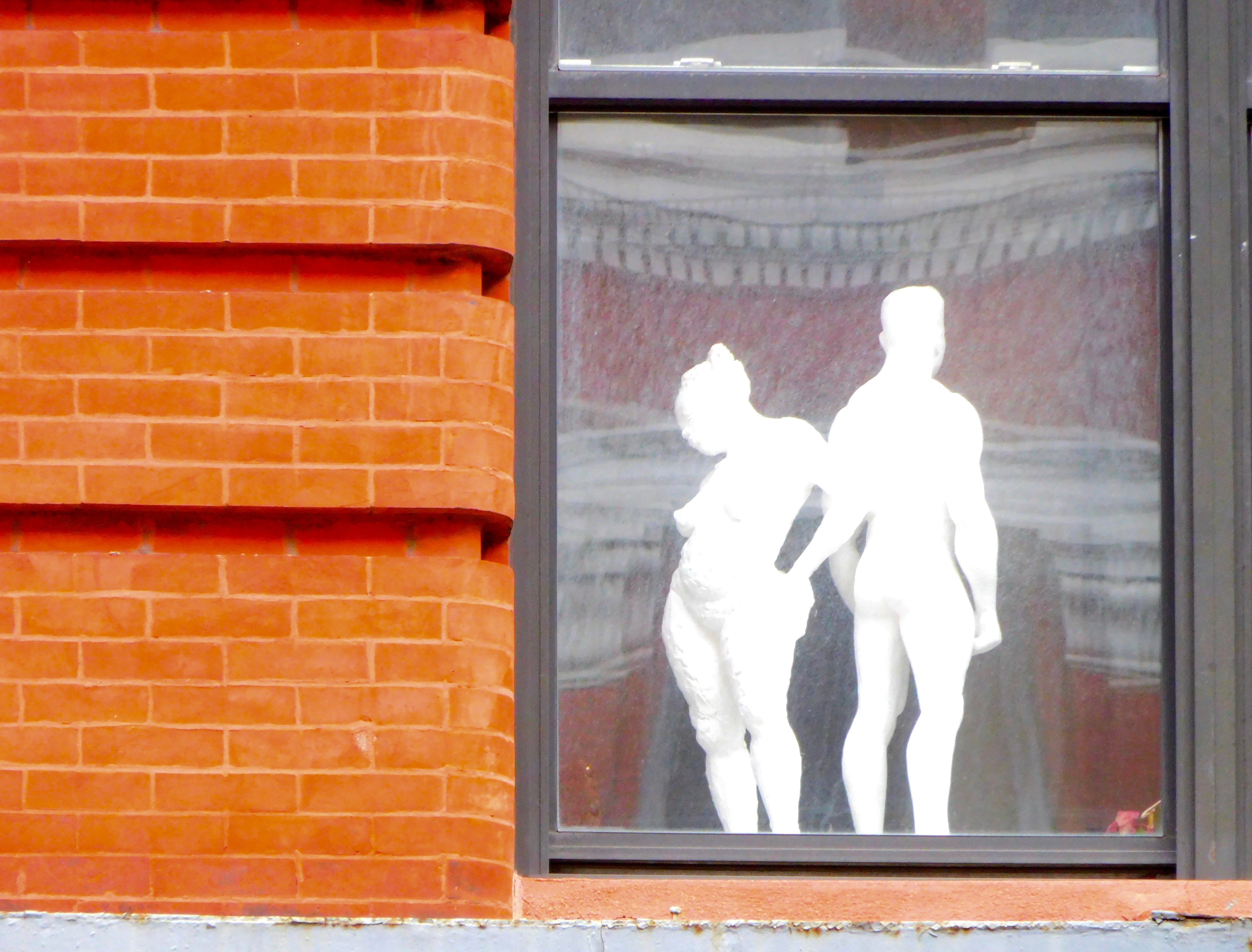 Two silhouettes stand in the window of a brick building.