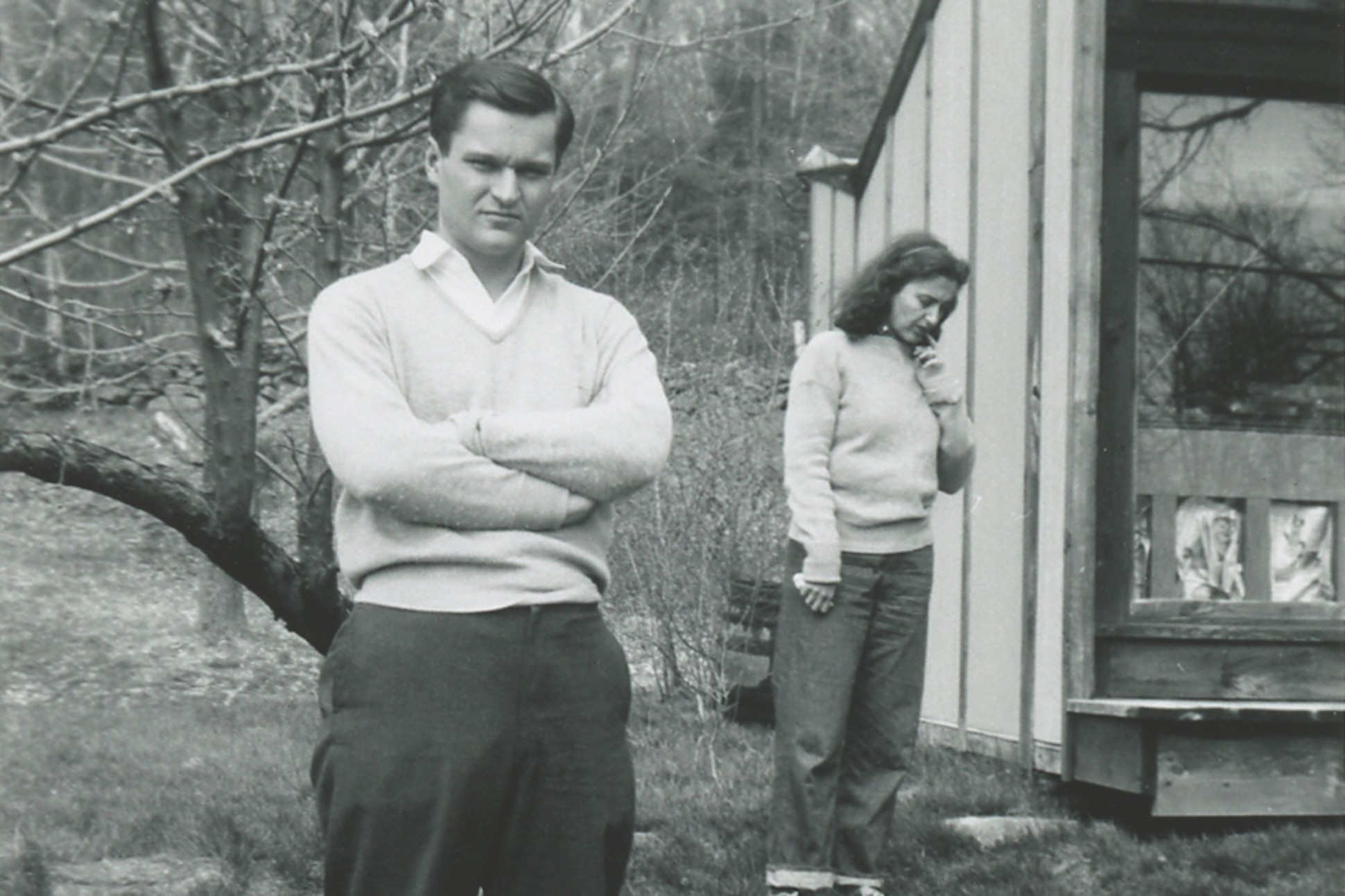 Black and white image of John Ashbery and Jane Freilicher standing near a building in Cornwall, Connecticut in 1954.