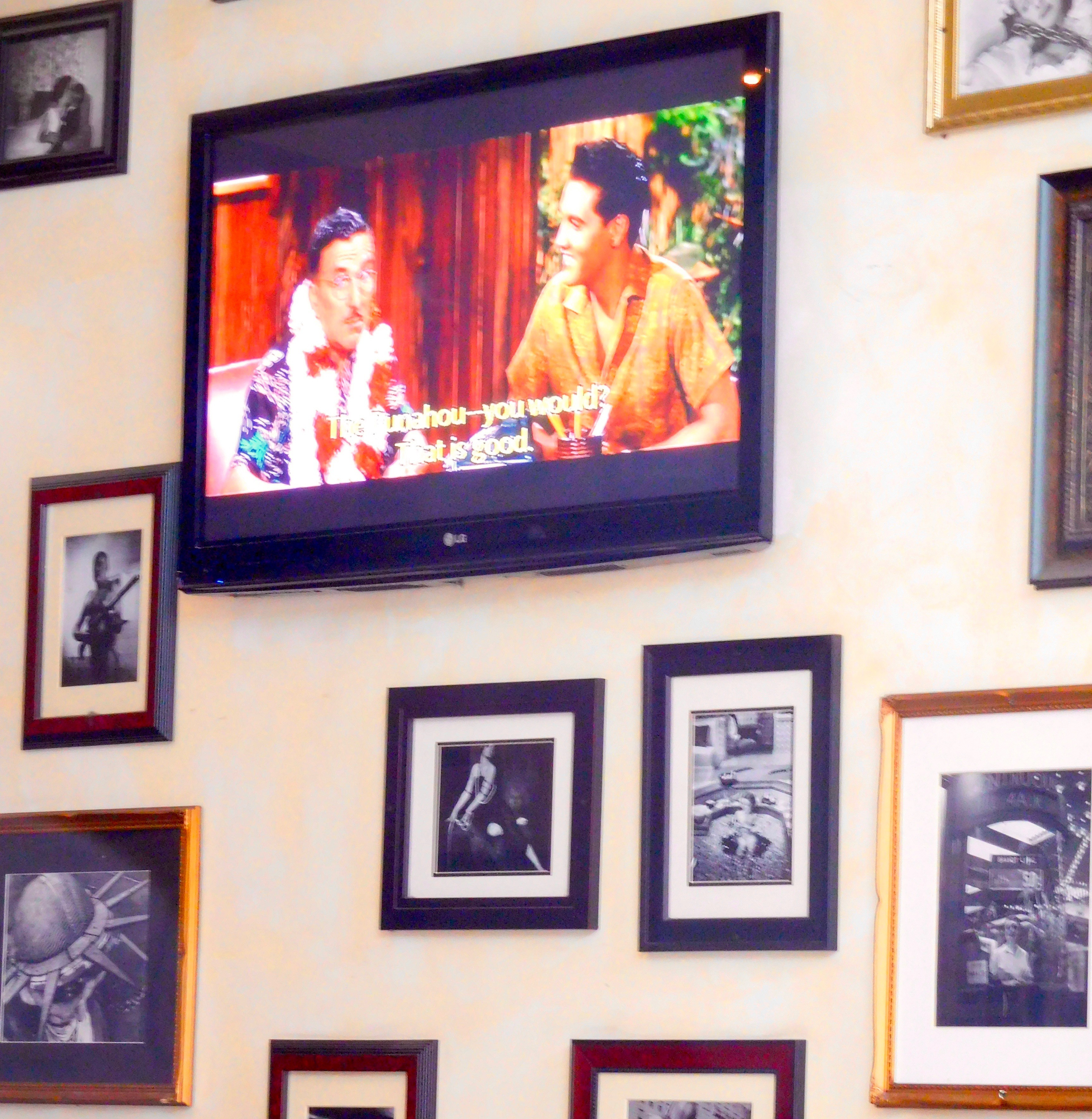 A TV is mounted on a wall amidst several framed photos