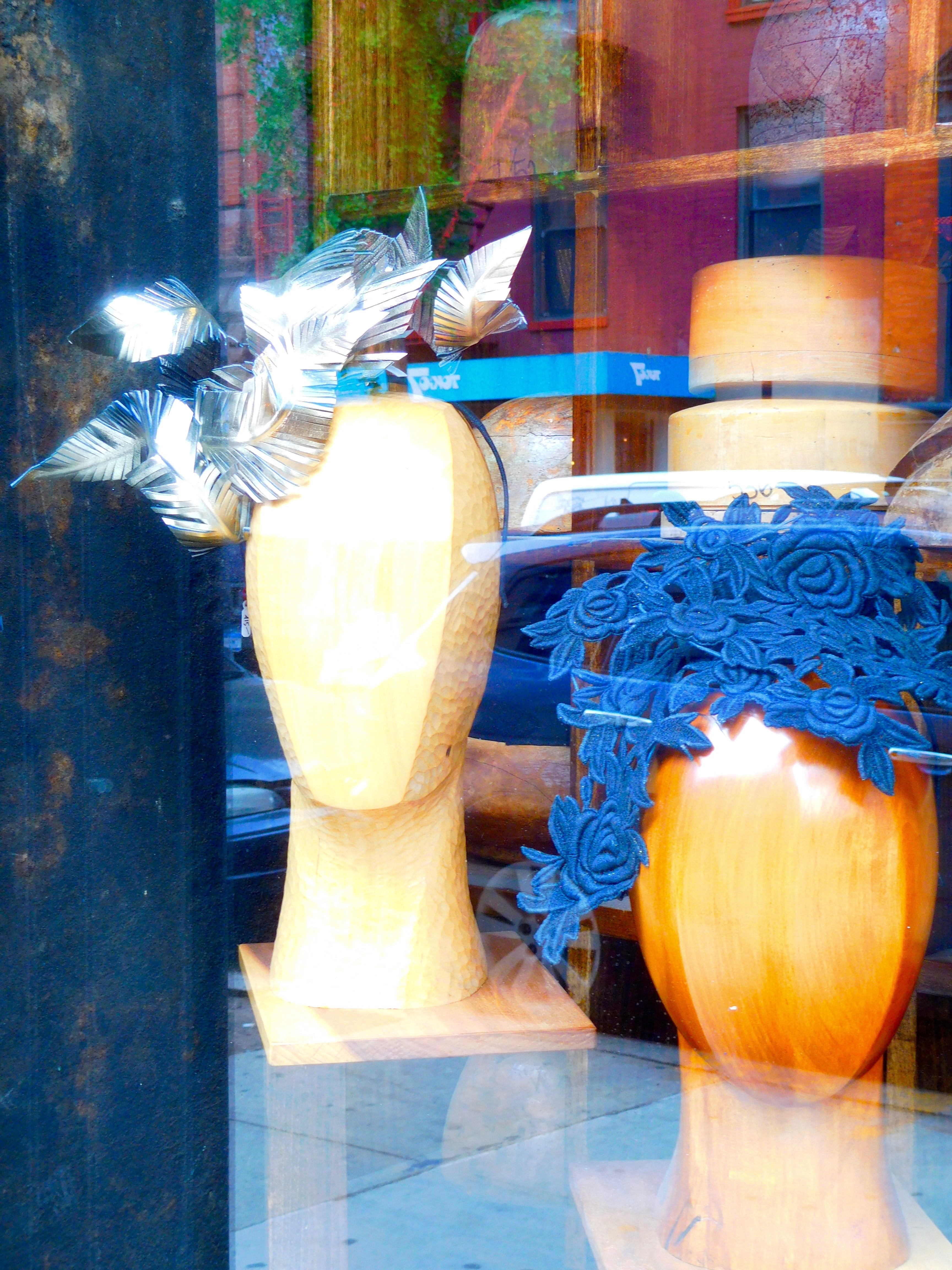 Two mannequin heads in a shop window wear artful headpieces.