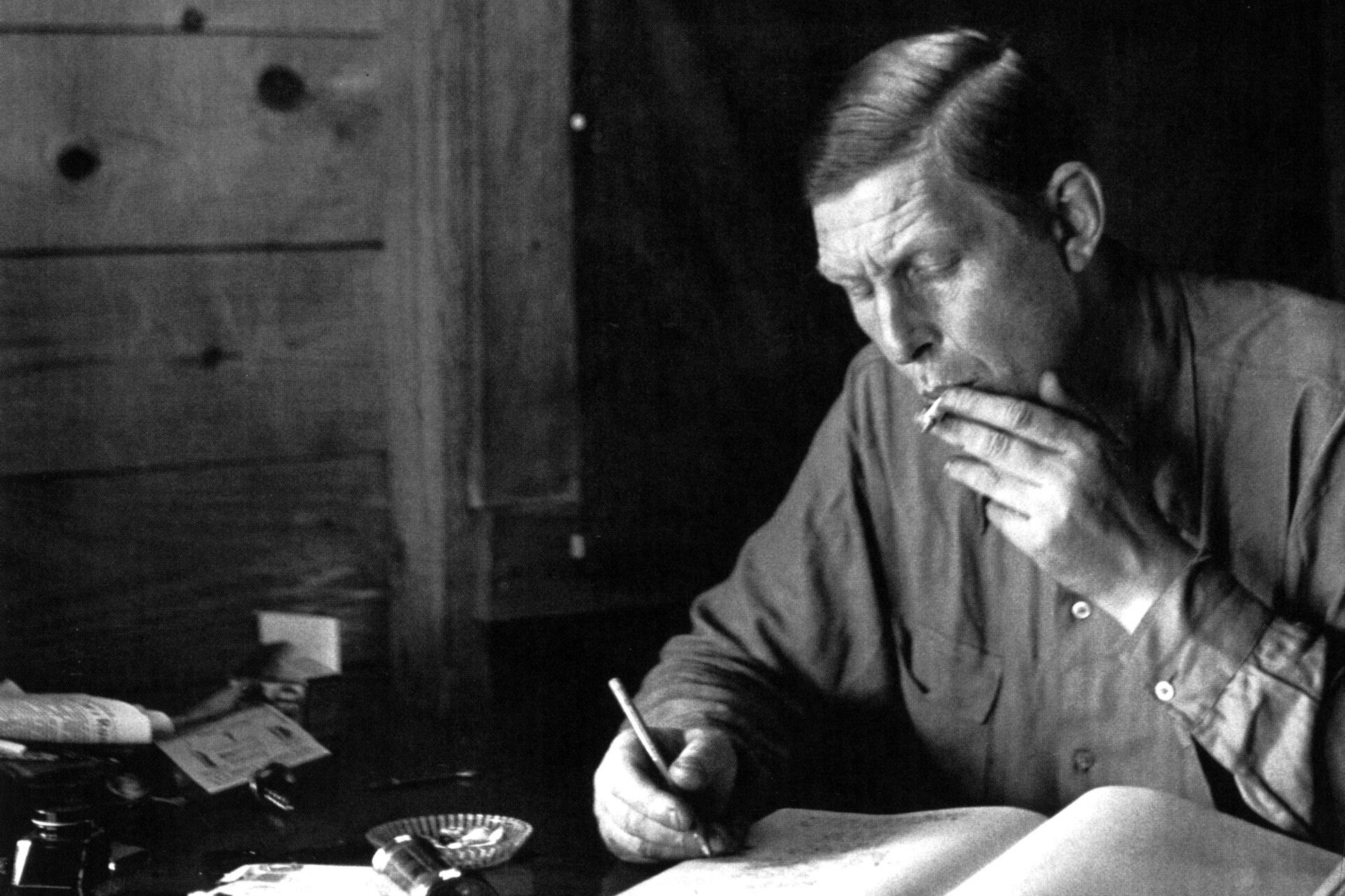 Black and white photograph of W.H. Auden smoking a cigarette and writing.