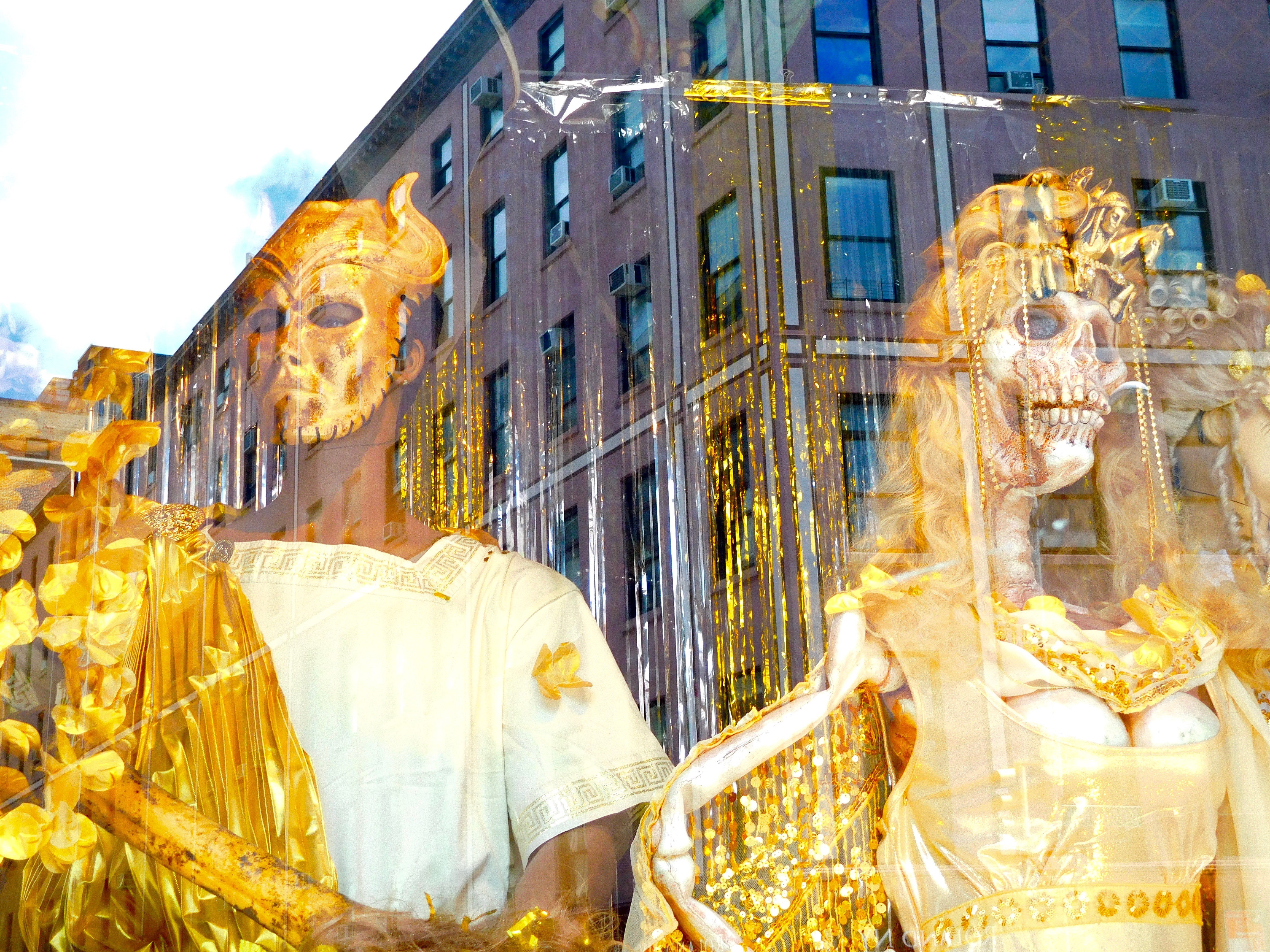 Two golden figures, one a skeleton, are displayed in a window that shows a reflection of the building behind it.