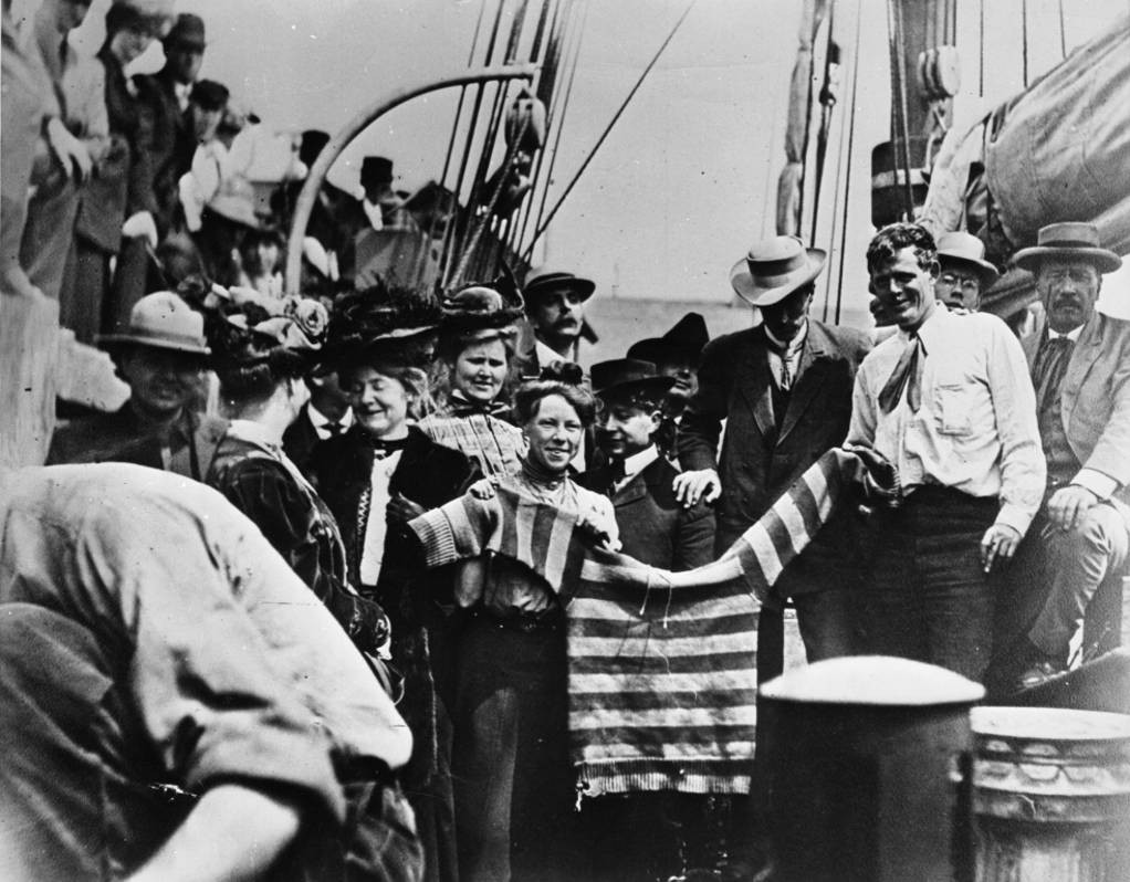 Black and white image of the writer Jack London and his wife, Charmian, on a ship holding out a college sweater, which was flown as a farewell gesture.