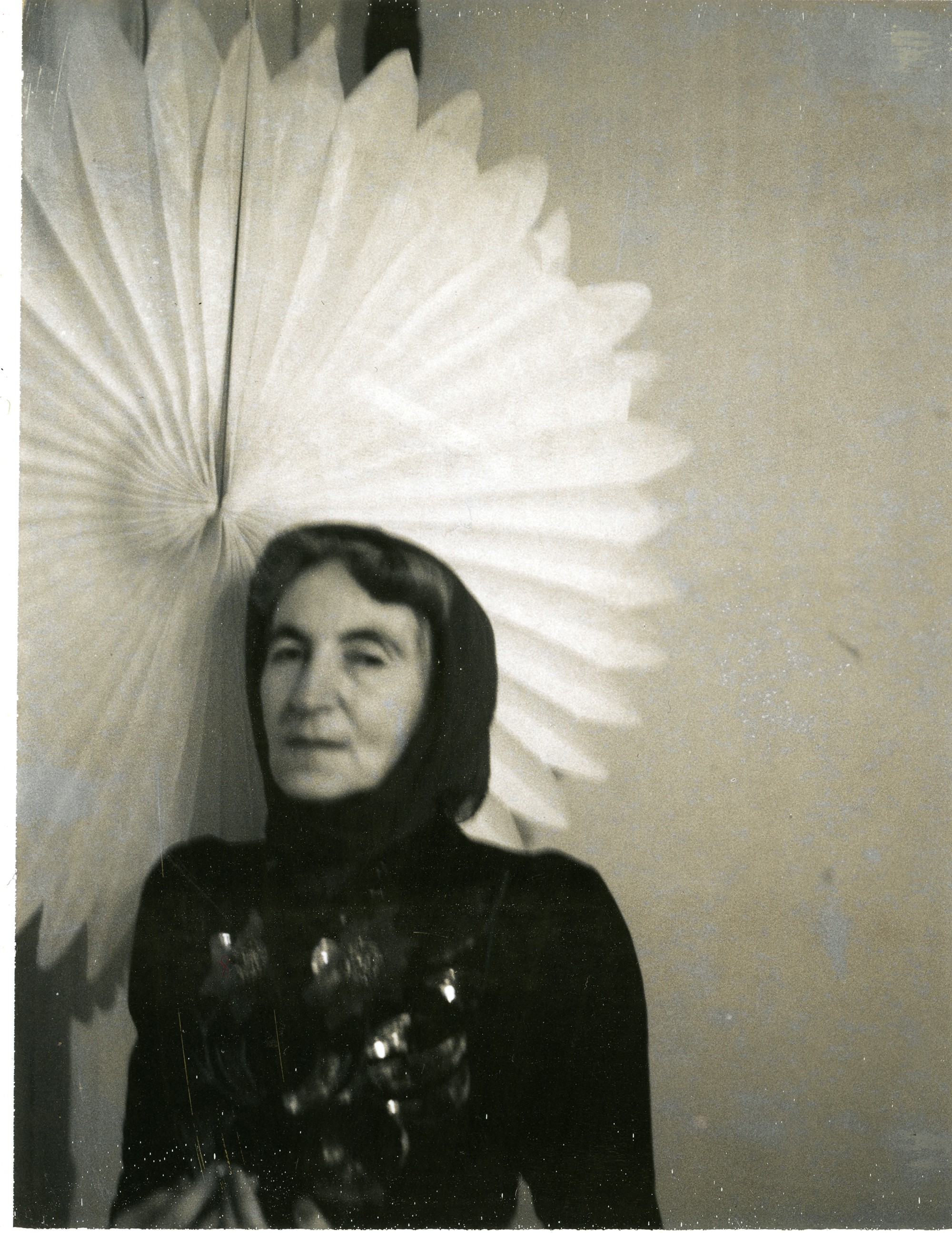 Helen Adam stands in a sparkling top and a head wrap, with a large white fan behind her.