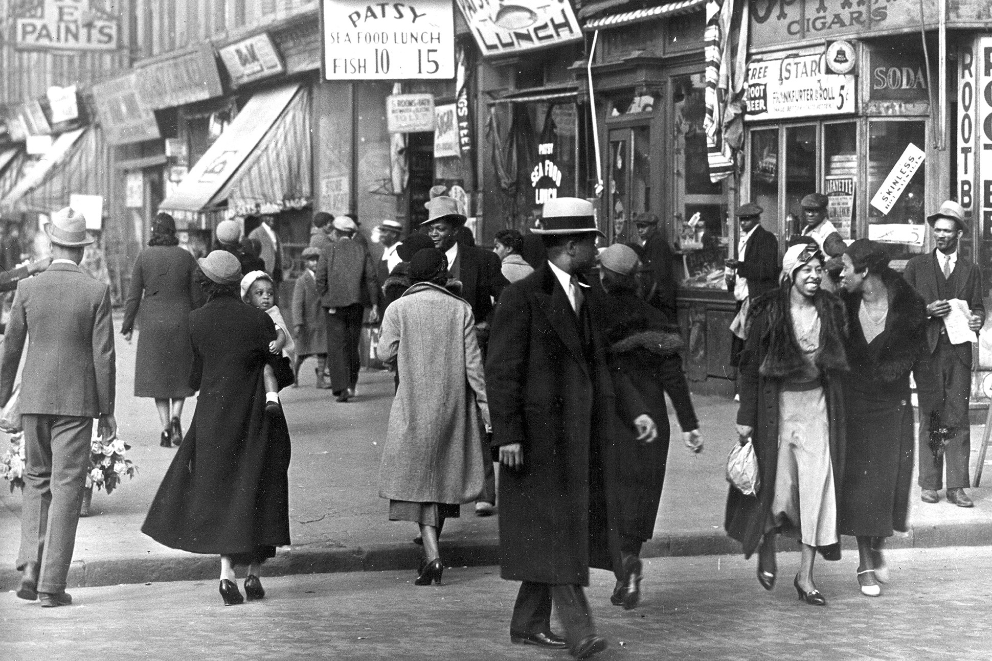 Black and white image of a street scene in Harlem in the 1930s.