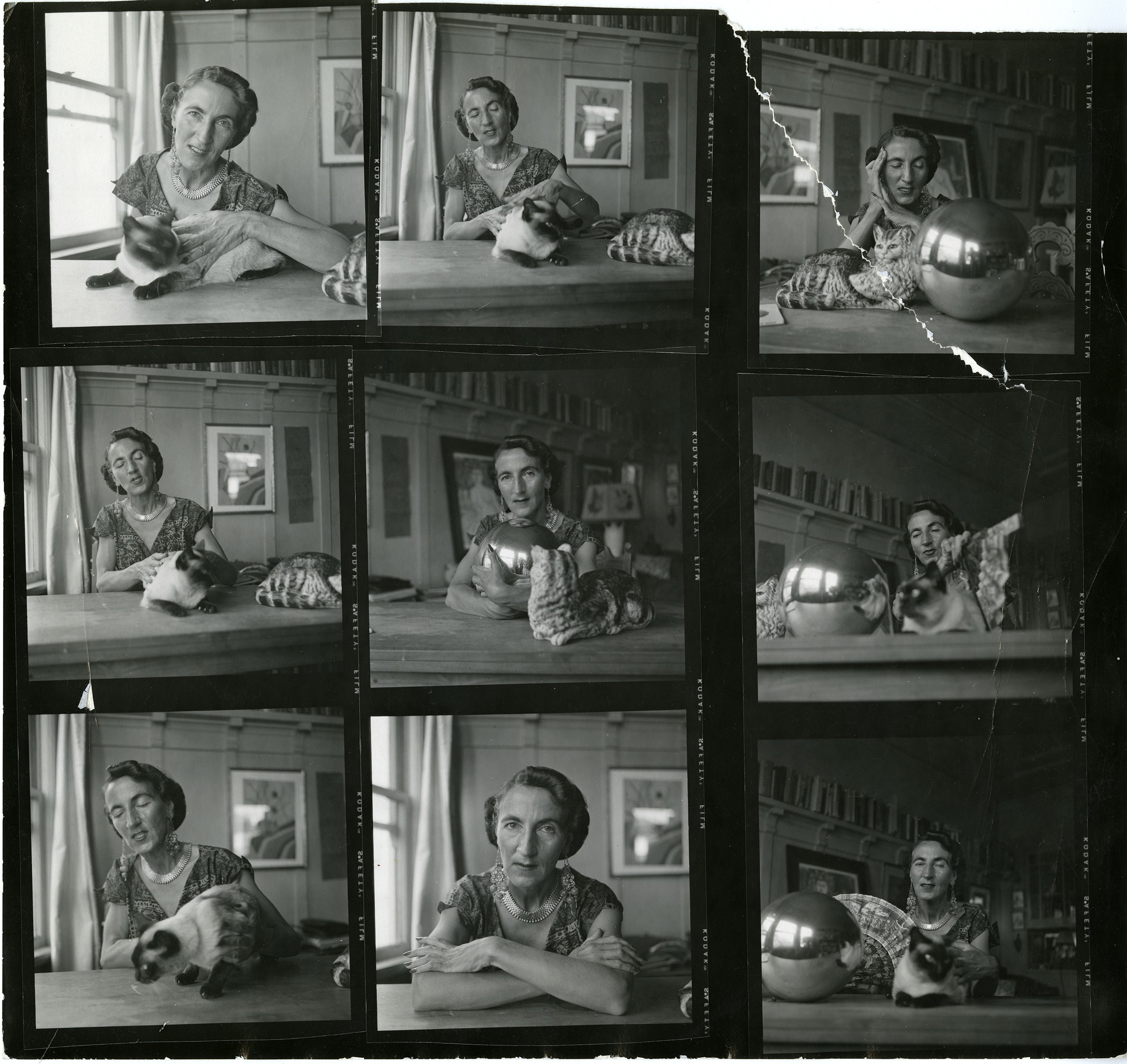 A contact sheet of nine photographs of Helen Adam, sometimes alone, sometimes with her cat, sometimes with cat and large metal sphere. There's a tear in the photograph at upper right.