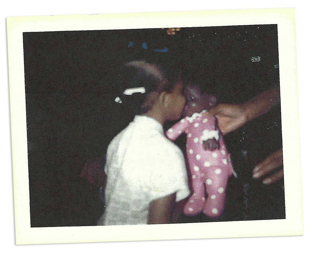 A scanned photograph of a young child face-to-face with a baby doll.