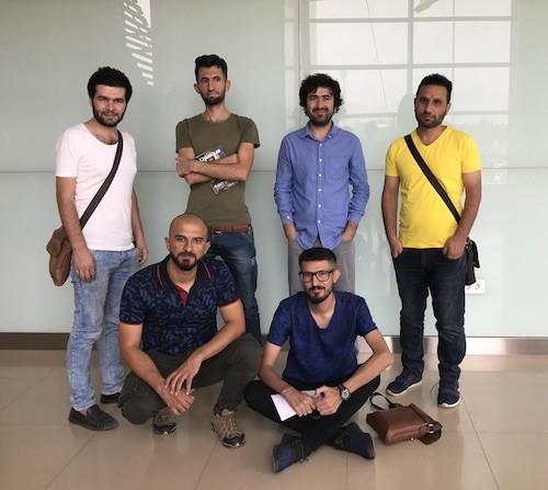 The six poets poets pose before their reading (L to R, front row: Emad, Zêdan; back row: Sardan, Saad, Zaeem, Jaff). Photo by Alana Marie Levinson LaBrosse.