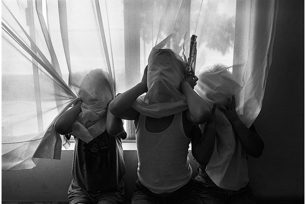 Photo of children covering their faces with a white curtain. Graciela Iturbide, Cholitos, White Fence, East Los Angeles, 1990