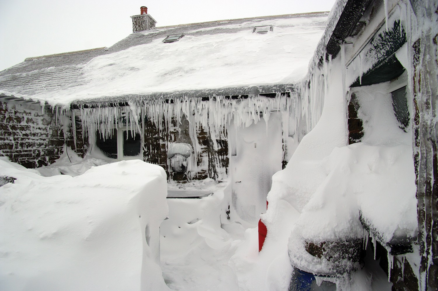 A house covered in snow and icicles.