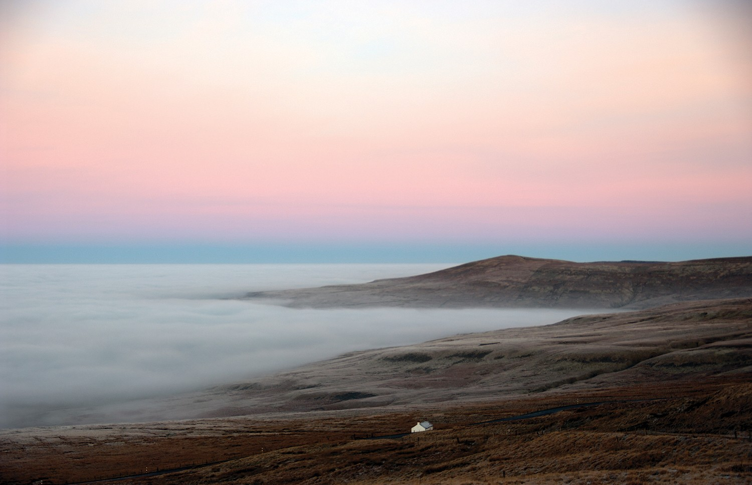 A landscape photo with fog and warm-colored, pink and orange sky.