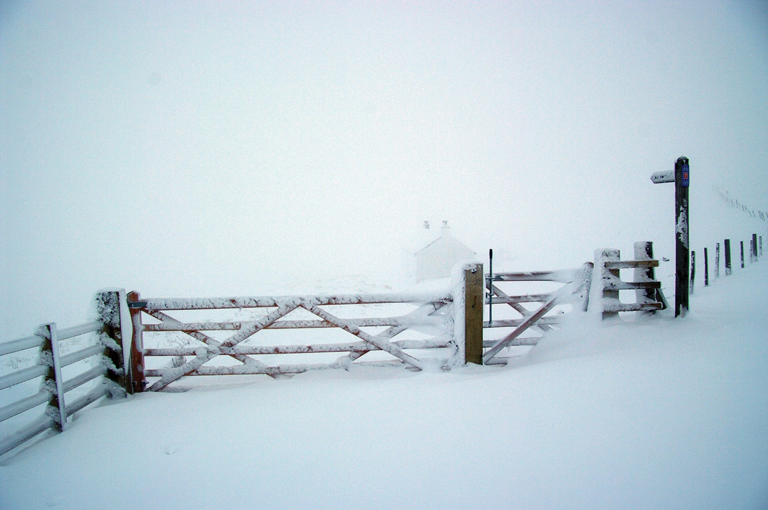 A barn gate covered in snow.