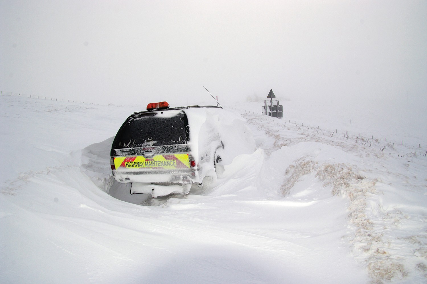 A highway maintenance vehicle covered in a snow drift on the road.